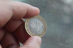 Um valor da moeda 1 lira turca entre os dedos da mão Fotos de Stock Royalty Free