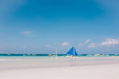 Um veleiro azul na praia branca da areia Céu nebuloso azul Imagem de Stock
