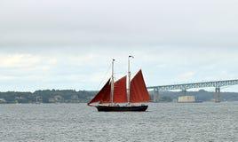 Um veleiro com velas e a ponte vermelhas de Newport fotos de stock