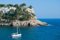 Um veleiro na frente de esse dos penhascos panorâmicos da ilha de Minorca fotografia de stock royalty free