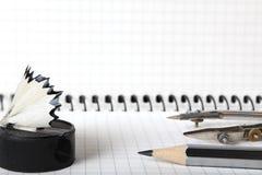 Um velho, de segunda mão, apontador com aparas, um lápis simples e compasso no caderno em uma caixa Foco seletivo Close-up Foto de Stock