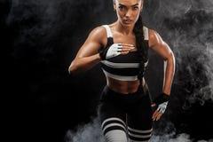 Um velocista atlético, fêmea forte, correndo no nascer do sol que veste no conceito da motivação do sportswear, da aptidão e do e foto de stock