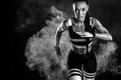 Um velocista atlético, fêmea forte, correndo no nascer do sol que veste no conceito da motivação do sportswear, da aptidão e do e imagem de stock royalty free