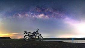 Um velomotor da silhueta sob uma Via Látea no campo Fotografia de Stock Royalty Free