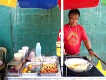 Um vendedor de alimento cozinha bolas de peixes, salsichas e ovos de codorniz que vende em um carro do alimento Foto de Stock Royalty Free