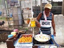 Um vendedor de alimento cozinha bolas de peixes, salsichas e ovos de codorniz que vende em um carro do alimento Fotos de Stock