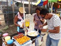 Um vendedor de alimento cozinha bolas de peixes, salsichas e ovos de codorniz que vende em um carro do alimento Fotografia de Stock Royalty Free
