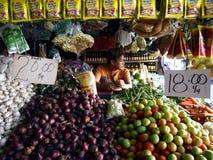 Um vendedor do mercado dentro de uma tenda das frutas e legumes em um mercado público fotografia de stock