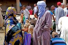 Um vendedor do remetente contratou com uma mulher do Berber no souk da cidade de Rissani em Marrocos Imagem de Stock Royalty Free