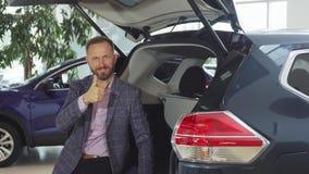 Um vendedor novo em um terno senta-se no tronco aberto do carro imagem de stock