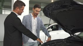 Um vendedor profissional coloca ao corrente um comprador com um motor de automóveis imagens de stock royalty free
