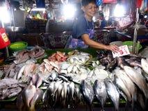 Um vendedor vende o tipo diferente dos peixes em um mercado molhado imagem de stock royalty free