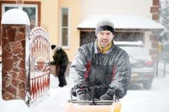 Um ventilador de neve do funcionamento do homem Fotos de Stock Royalty Free