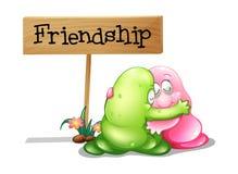 Um verde e um monstro cor-de-rosa que abraçam perto do signage de madeira Fotografia de Stock Royalty Free