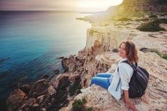 Um viajante à moda da jovem mulher olha um por do sol bonito no fotos de stock