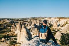 Um viajante com uma trouxa senta-se sobre as montanhas e mostra-se sua mão em uma vista bonita em Cappadocia em Turquia Imagem de Stock Royalty Free