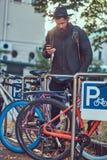 Um viajante considerável do moderno com uma barba à moda e tatuagem em h foto de stock