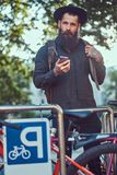 Um viajante considerável do moderno com uma barba à moda e a tatuagem em seus braços vestiram-se na roupa ocasional e no chapéu,  fotografia de stock