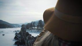 Um viajante da moça toma uma foto em um smartphone Fotografa um rio congelado do inverno Um chapéu e um ` s do viajante backpack video estoque