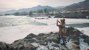 Um viajante da moça toma uma foto em um smartphone Fotografa um rio congelado do inverno Um chapéu e um ` s do viajante backpack filme