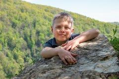 Um viajante do menino escalou ? parte superior do penhasco imagem de stock royalty free