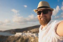 Um viajante farpado vermelho do moderno nos óculos de sol e no chapéu faz o selfie em férias no fundo do litoral imagens de stock royalty free