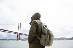 Um viajante novo ou um turista com uma trouxa na margem em Lisboa em Portugal ao lado do 25o de April Bridge Fotografia de Stock Royalty Free