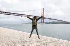Um viajante novo ou um turista com uma trouxa na margem em Lisboa em Portugal ao lado do 25o de April Bridge Imagem de Stock