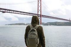 Um viajante novo ou um turista com uma trouxa na margem em Lisboa em Portugal ao lado do 25o de April Bridge Fotografia de Stock