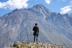 Um viajante que olha na paisagem da montanha, montanha de Kazbeg - Kazbegi (Stepantsminda), Geórgia fotos de stock