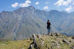 Um viajante que olha na paisagem da montanha, montanha de Kazbeg - Kazbegi (Stepantsminda), Geórgia imagens de stock royalty free