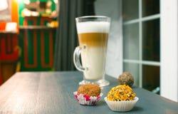 Um vidro alto enchido com um latte mergulhado do café em uma tabela de madeira com bolas do bolo fotografia de stock