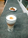 Um vidro alto enchido com um latte mergulhado do café em uma tabela de madeira com bolas do bolo imagens de stock royalty free