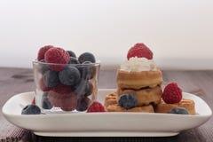 Um vidro com framboesas e mirtilos, ao lado dele é waffles com framboesas e chantiliy fotos de stock royalty free