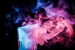 Um vidro com fumo colorido fotografia de stock
