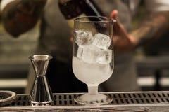 Um vidro com o cocktail alcoólico que está no contador da barra Processo de mistura da bebida do álcool Tendências modernas na in fotografia de stock royalty free