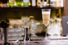 Um vidro com o cocktail alcoólico que está no contador da barra Processo de mistura da bebida do álcool Tendências modernas na in fotos de stock