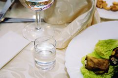 Um vidro com vodca em uma tabela do serviço Close-up fotos de stock