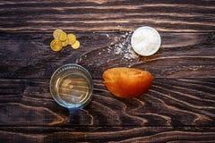 Um vidro da água e de uma parte de pão na tabela na frente de t imagens de stock
