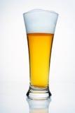 Um vidro da cerveja com um tampão da espuma. Foto de Stock