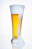 Um vidro da cerveja com um tampão da espuma. Com uma grande espuma do gotejamento. Foto de Stock