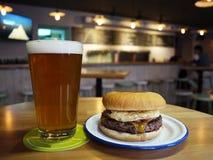 Um vidro da cerveja e de um Hamburger Alimento bonito e delicioso, cerveja espumosa em um vidro detalhes fotos de stock royalty free