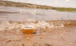 Um vidro da cerveja na água imagem de stock royalty free