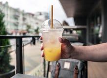 Um vidro da limonada fresca, fresco Foto do suco com um gelo contra um backdoor da cidade fotografia de stock