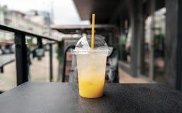 Um vidro da limonada fresca, fresco Foto do suco com um gelo contra um backdoor da cidade imagens de stock