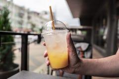 Um vidro da limonada fresca, fresco Foto do suco com um gelo contra um backdoor da cidade imagens de stock royalty free