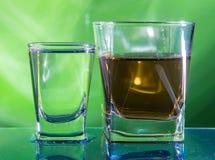 Um vidro da vodca e um vidro da aguardente, do uísque ou do bourbon em um branco ou em um fundo colorido Foto de Stock
