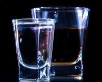 Um vidro da vodca e um vidro da aguardente, do uísque ou do bourbon em um branco ou em um fundo colorido Fotografia de Stock Royalty Free