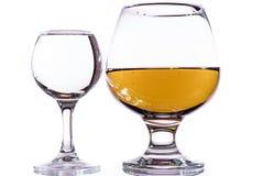 Um vidro da vodca e um vidro da aguardente, do uísque ou do bourbon em um branco ou em um fundo colorido Imagem de Stock