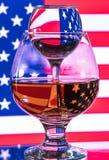 Um vidro da vodca e um vidro da aguardente, do uísque ou do bourbon em um branco ou em um fundo colorido Imagens de Stock